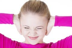 Nahaufnahme der frustrierten jungen Frau, die ihre Ohren hält. stockfotografie