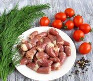 Nahaufnahme der gefrorenen rohen Huhninnerer Nahaufnahme von neuen rohen Hühnerherzen mit Tomate und Dill Stockfotografie