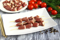 Nahaufnahme der gefrorenen rohen Huhninnerer Nahaufnahme von neuen rohen Hühnerherzen mit Tomate und Dill Lizenzfreie Stockfotografie