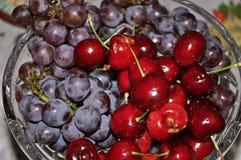 Nahaufnahme der Glasschüssel voll köstlicher Trauben und Kirschen Lizenzfreies Stockfoto