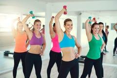 Nahaufnahme der Gruppe junger Frauen, die Übung mit Dummköpfen auf Trizeps tun Stockbilder
