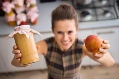 Nahaufnahme der Hände der Frau, die Apfelsauce und frischen Apfel halten Lizenzfreie Stockfotos