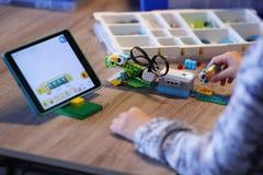 Nahaufnahme der Hände des Jungen, die Roboter konstruieren und in der Schule ihn an der Robotiklektion programmieren lizenzfreies stockbild