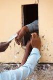 Nahaufnahme der Hände des Mannes, die Alkohol durch kleines Fenster, Delh kaufen Stockfotografie