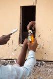 Nahaufnahme der Hände des Mannes, die Alkohol durch kleines Fenster, Delh kaufen Lizenzfreie Stockbilder
