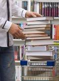 Nahaufnahme der Hände, die Bücher in Korb einsetzen Lizenzfreies Stockfoto