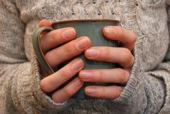 Zwei Hände, die einen Becher des Getränks halten Stockbilder