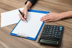 Nahaufnahme der Hände einer Geschäftsfrau beim etwas wesentliche quantitative Informationen notieren Lizenzfreie Stockfotografie