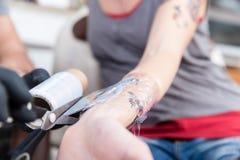 Nahaufnahme der Hände eines erfahrenen Tätowierungskünstlers Stockfotos