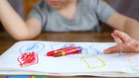 Nahaufnahme der Hände eines Kindes, das auf Papier mit einem hellen gelben Bleistift oder einer Kreide zeichnet, die am Tisch sit stock footage