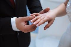 Nahaufnahme der Hände der Männer und Frauen, die heiraten Ein Mann setzt an einen Ehering auf ein schlankes, würdevoll stockfoto