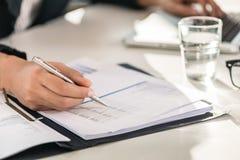 Nahaufnahme der Hände der Zahlen einer Geschäftsfrau-Prüfung lizenzfreie stockbilder