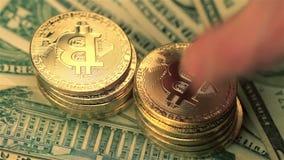Nahaufnahme der Hand bitcoin goldene Münzenstapel auf Dollarbanknoten setzend stock video footage