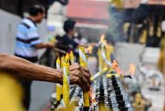 Nahaufnahme der Hand brennende Kerze auf den Kerzenhalter setzend Stockbild