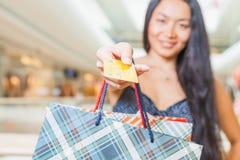 Nahaufnahme der Hand der asiatischen Frau, die Kreditkarte und Taschen hält Lizenzfreie Stockfotografie