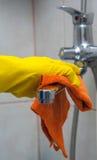 Nahaufnahme der Hand der Frau mit dem gelben Handschuh, der Hahn abwischt Stockbilder