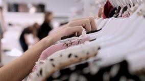 Nahaufnahme der Hand des Mädchens in einem Bekleidungsgeschäft, das ein stilvolles Sommerkleid wählt Einkaufen am Kleidungsausste stock footage
