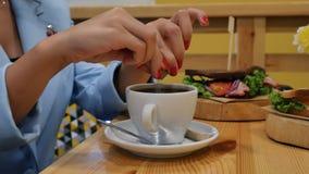 Nahaufnahme der Hand des Mädchens mit roter Maniküre bricht Zuckerstock in der Mitte und gießt Zucker in eine Schale mit neuer Ka stock video