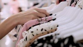 Nahaufnahme der Hand des M?dchens in einem Bekleidungsgesch?ft, das ein stilvolles Sommerkleid w?hlt Einkaufen am Kleidungsausste stock video footage
