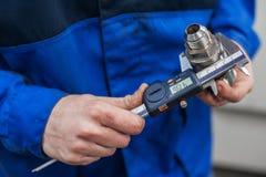 Nahaufnahme der Hand einer Arbeitskraft, die ein Teil vom Mechanismus eines genauen Messgeräts misst Elektronischer Schieber stockbilder