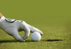 Nahaufnahme der Hand einer Person, die einen Golfball nahe einem Loch setzt Stockfotografie