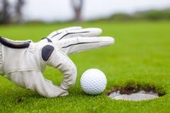 Nahaufnahme der Hand eines Mannes, die Golfball in Loch einsetzt Stockfotografie