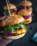 Nahaufnahme der Hand selbst gemachten frischen Burger halten lizenzfreie stockfotografie