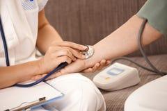 Nahaufnahme der Hand unter Verwendung des Stethoskops auf Handgelenk Stockfotos
