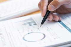 Nahaufnahme der Handgeschäftsmannlesung und -schreibens mit unterzeichnendem Vertrag des Stiftes über Dokument für das Ausfüllen  stockfotografie