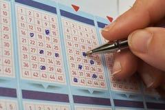 Nahaufnahme der Handmarkierungsnummer auf Lottoschein mit Stift Stockfotografie