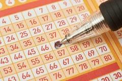 Nahaufnahme der Handmarkierungsnummer auf Lottoschein mit Stift Stockbild