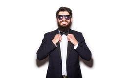 Nahaufnahme der hübschen tragenden Sonnenbrille des jungen Mannes, die seine Fliege justiert und Kamera betrachtet Stockfoto
