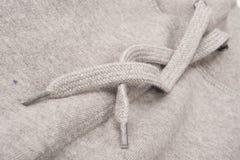 Nahaufnahme der Hoodie-Spitzes von Grey Sweatshirt Stockbilder