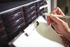 Nahaufnahme der Instandhaltungsaufzeichnung des Technikers des Gestells brachte Server am Klemmbrett an Stockbilder