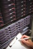 Nahaufnahme der Instandhaltungsaufzeichnung des Technikers des Gestells brachte Server am Klemmbrett an Lizenzfreie Stockfotos
