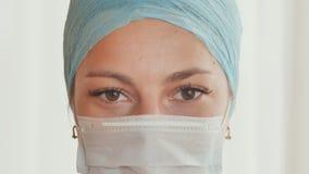 Nahaufnahme der jungen Ärztin mit einer Maske auf Gesicht stock video