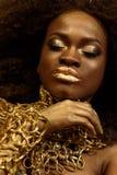 Nahaufnahme der jungen Afroamerikanerfrau mit geschlossenen Augen und goldenem Zubehör, Make-up, Hand unter dem Kinn halten lizenzfreies stockfoto