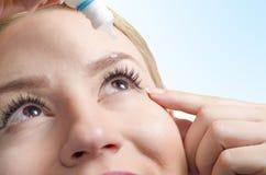 Nahaufnahme der jungen Frau Augentropfen anwendend stockfotos