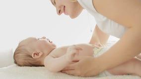 Nahaufnahme der jungen Mutter ihr Baby streichelnd und küssend, das auf Bett liegt stock footage