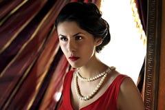 Nahaufnahme der jungen schönen Frau im roten Kleid Stockfotografie