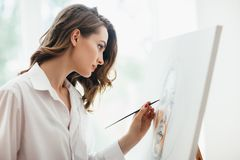 Nahaufnahme der jungen Schönheitsmalerei auf Segeltuch im Studio lizenzfreie stockbilder
