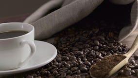 Nahaufnahme der Kaffeetasse mit Röstkaffeebohnen auf hölzernem Hintergrund stock video footage