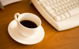 Nahaufnahme der Kaffeetasse nahe Tastatur Lizenzfreie Stockfotografie