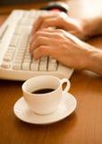 Nahaufnahme der Kaffeetasse nahe Tastatur Lizenzfreies Stockfoto
