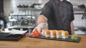 Nahaufnahme - der Kellner setzte die Sushi an Bord auf dem Tisch in Restaurant ein Lizenzfreie Stockbilder