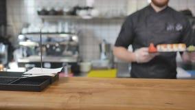 Nahaufnahme - der Kellner setzte die Sushi an Bord auf dem Tisch in Restaurant ein Stockfotos