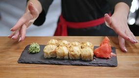 Nahaufnahme - der Kellner setzte die Sushi an Bord auf dem Tisch in Restaurant ein Lizenzfreie Stockfotografie
