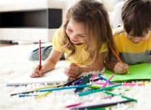 Nahaufnahme der Kinder, die liegend auf dem Fußboden zeichnen Stockfotos