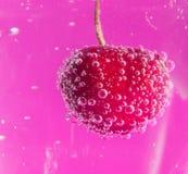 Nahaufnahme der Kirsche im Wasser mit Blasen auf einem rosa Hintergrund Lizenzfreies Stockfoto