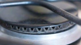 Nahaufnahme der kleinen blauen Flamme des Gases auf einem Gasherd t?tigkeit Mahlzeit-Vorbereitung stockfotos